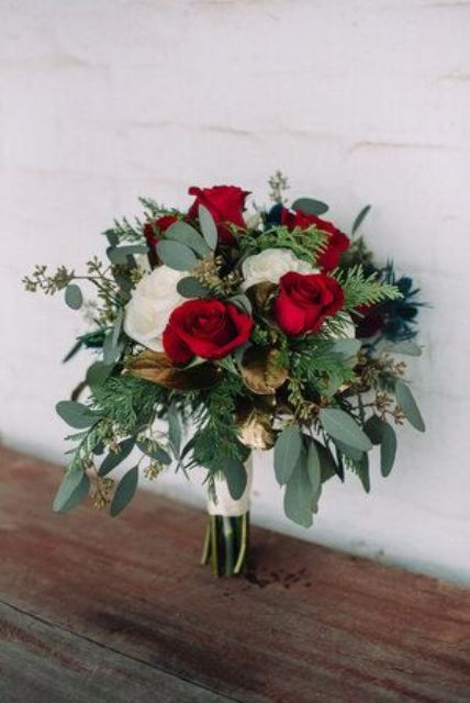a luxurious red and white rose wedding bouquet with greenery and ferns and some gilded leaves is pure love for a Valentine's Day bride