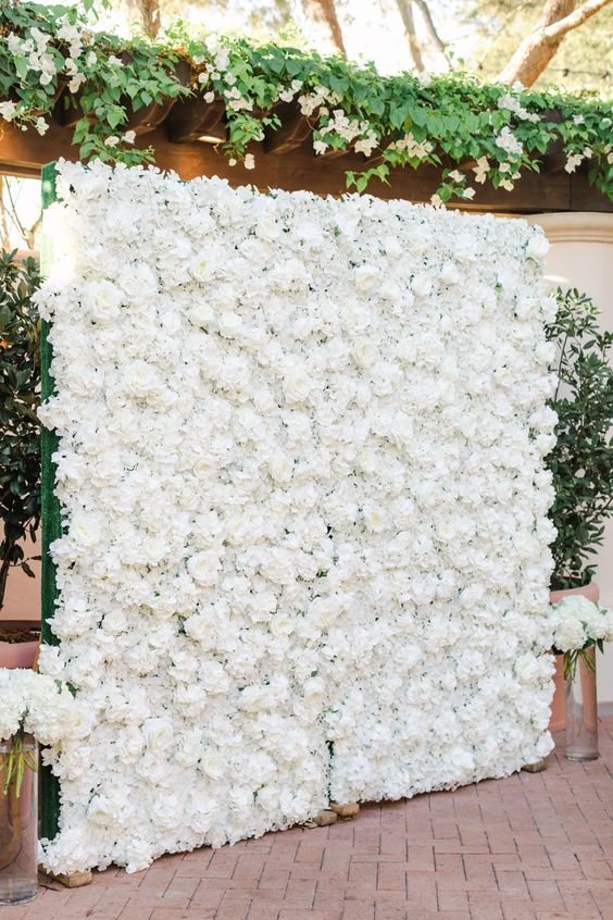 a luxury white rose and hydrangea floral wall backdrop can work both for the ceremony and for takign photos