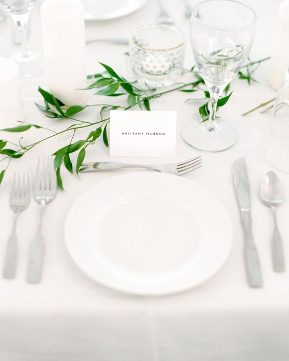 a minimalist and airy tablescape in white, with candles and a touch of fresh greenery