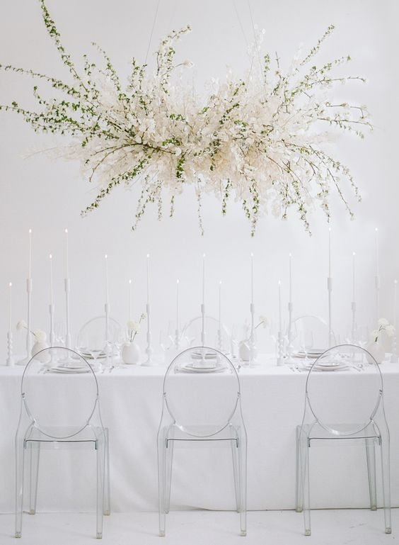 a minimalist ethereal wedding reception space with an oversized overhead floral decoration, sheer chairs and everything white
