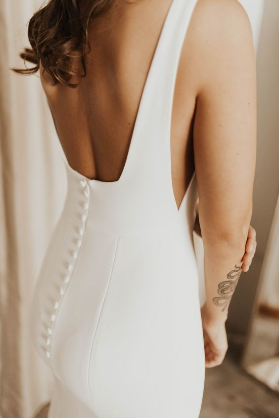 a minimalist plain sheath wedding dress with a cutout back on buttons looks wow
