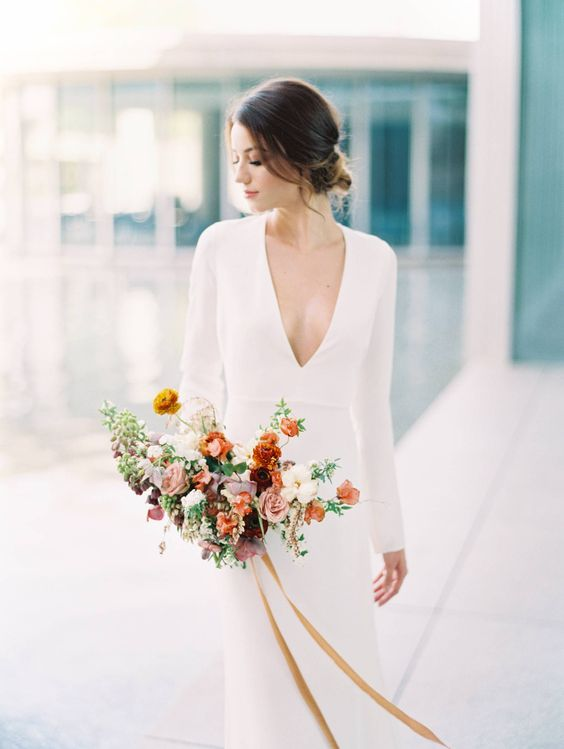 a minimalist plain sheath wedding dress with long sleeves and a plunging neckline