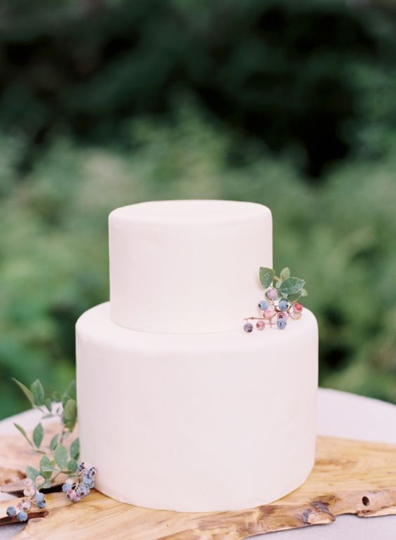 a minimalist plain white wedding cake topped with some berries for a modern natural or minimalist wedding