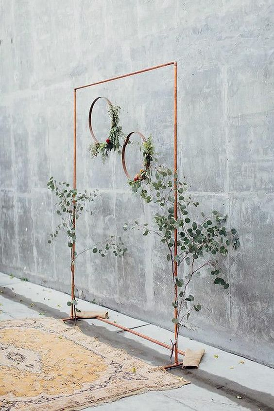 a minimalist wedding arch of copper, with greenery and copper hoops hanging from it
