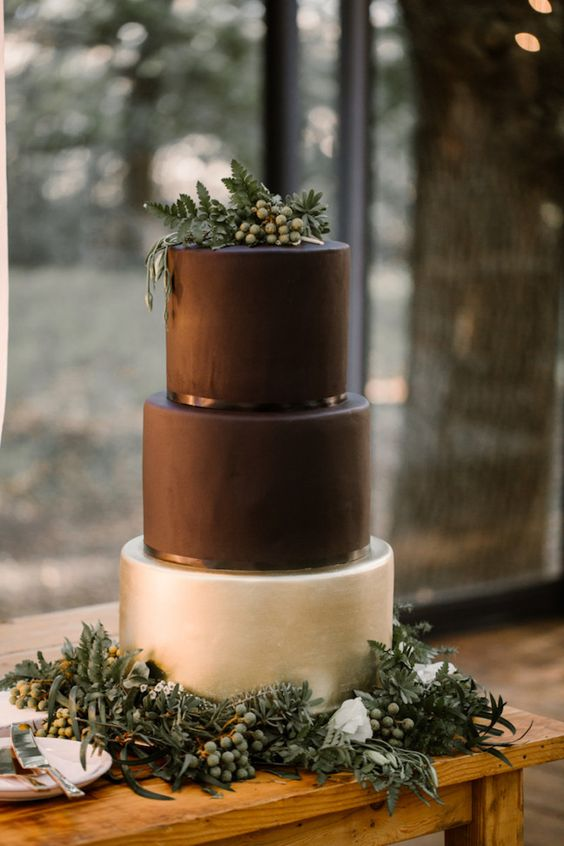 a minimalist wedding cake in black and pearly, with fresh greenery and berries on top