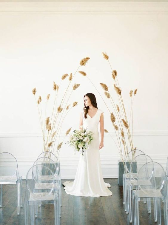 a minimalist wedding ceremony space with clear chairs and soem dried herbs for creating an altar