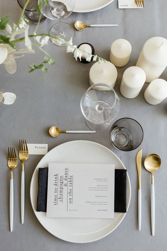 a minimalist wedding tablescape with a grey tablecloth, gold cutlery, neutral blooms and pillar candles