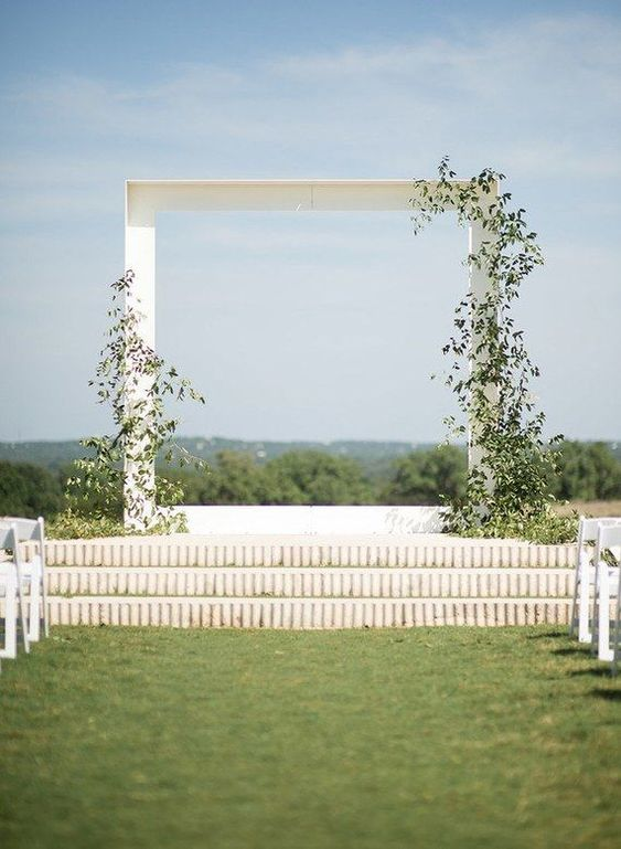 a minimalist white wedding arch decorated with lush foliage is a stylish idea