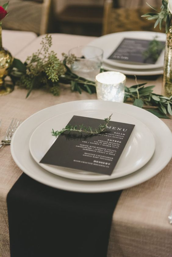 a minimalist winter wedding tablescape done in neutrals and black, with greenery and gilded touches