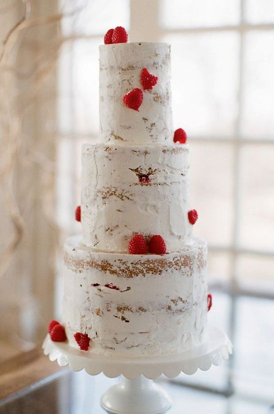 a naked wedding cake decorated with strawberries looks lovely, tasty and very cool, ideal for a Valentine wedding