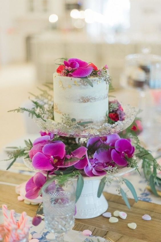 a naked wedding cake served with hot pink blooms and greenery is adorable for Valentine's Day