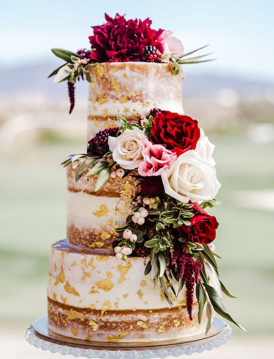 a naked wedding cake with gold leaf, pink, white and red blooms and greenery and some berries is fantastic