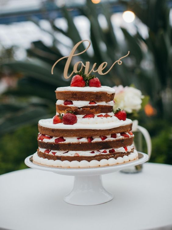 a naked wedding cake with strawberries and a gold LOVE topper is amazing and bold