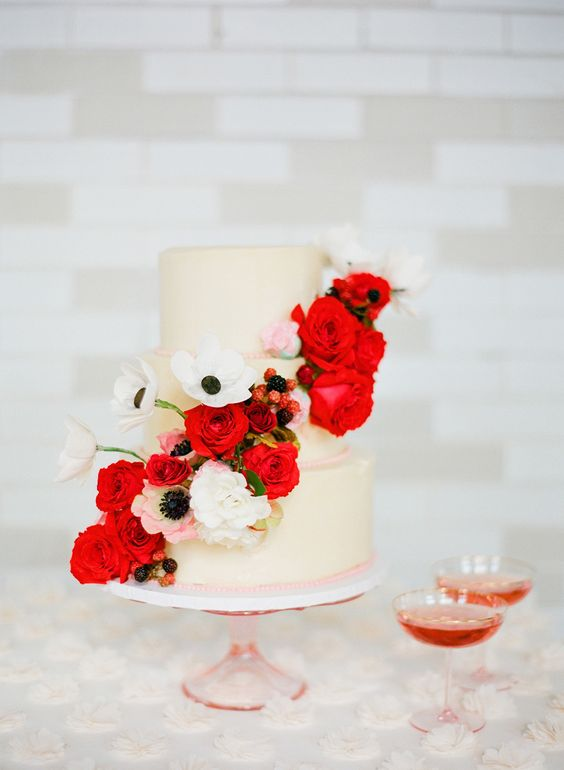 a neutral wedding cake with white and red blooms and berries is a traditionally cool idea for a Valentine wedding