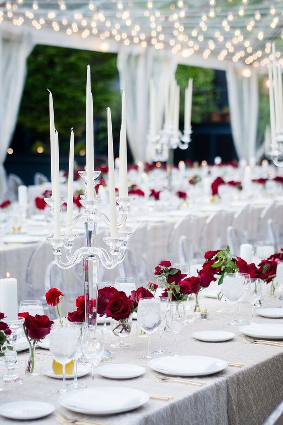 a neutral wedding tablescape with a shiny silver tablecloth, red roses, crystal candelabras and some greenery is a modern take on classics