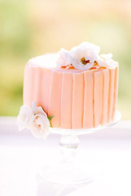 a peachy shard wedding cake decorated with white and blush blooms for a Valentine's Day