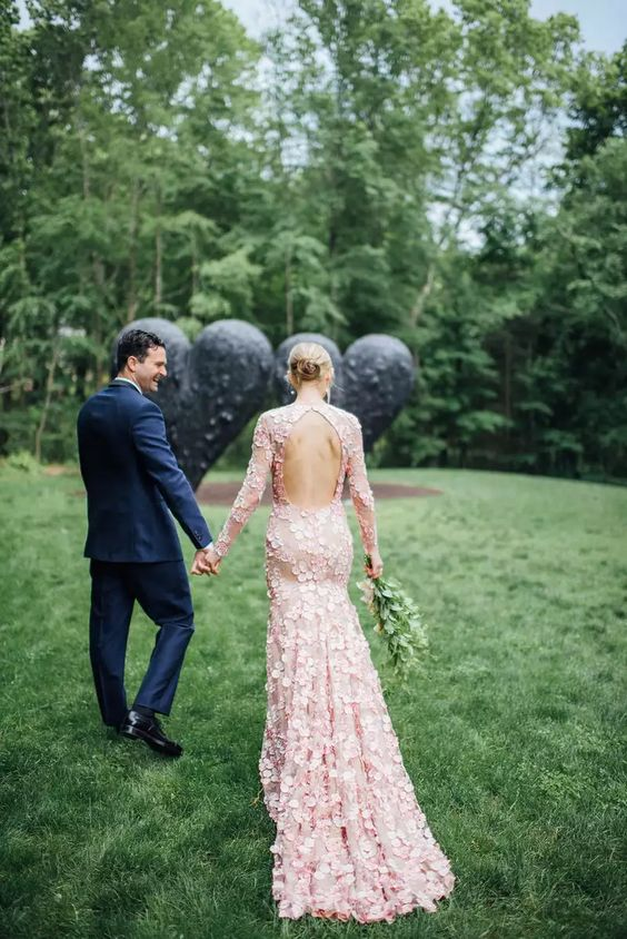 a bride in a trendy pink wedding dress and a groom in a blue suit