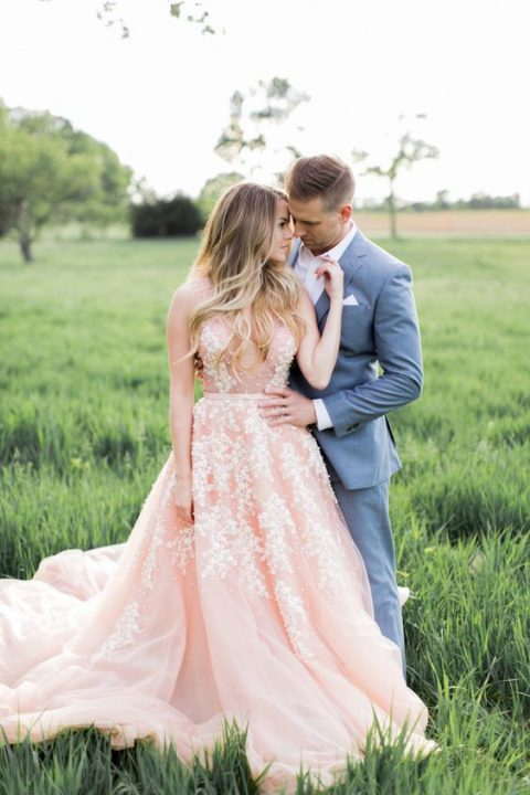 a pink sleeveless wedding dress with a trendy plunging neckline and pearl floral embroidery all over the gown