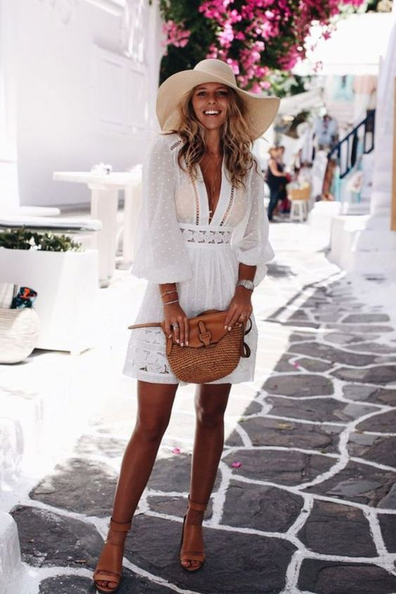 a polka dot A-line mini dress with a plunging neckline, puff sleeves, boho lace inserts, nude heels and a large hat for a tropical wedding
