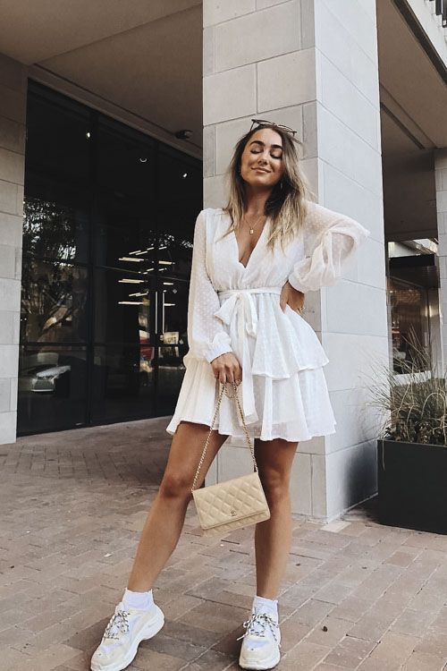 a pretty a-line mini dress with a deep neckline, long sleeves and a ruffle tiered skirt, trainers and a mini bag for a relaxed look