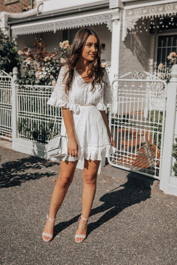 a pretty boho lace mini dress with a V-neckline, ruffles, bell sleeves, nude shoes and a white bag for a casual wedding