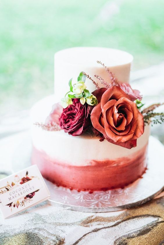 a pretty ombre pink wedding cake topped with burgundy, red and blush ones and greenery is ideal for Valentine weddings
