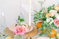 a pretty pastel Valentine's Day wedding table with woven chargers, blush plates, gold candleholders and calligraphy, candles and citrus