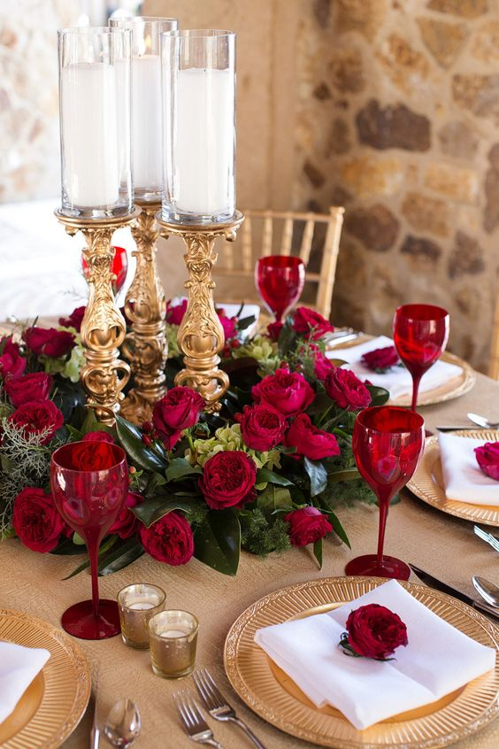a refined Valentine's Day wedding centerpiece of greenery, red roses, refined gold candleholders and red glasses to match