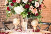 a refined Valentine's Day wedding table with gold cutlery, gold rimmed chargers, a bold floral centerpiece and burgundy napkins
