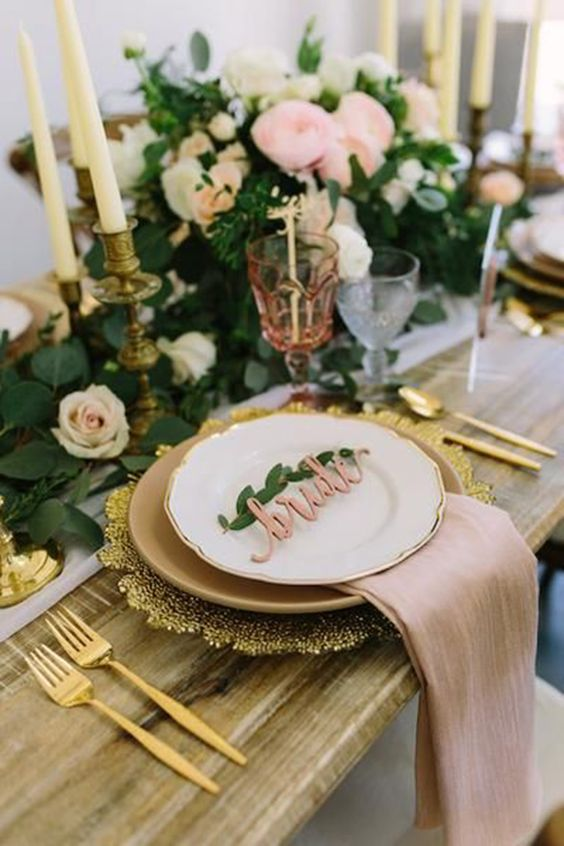 a refined and beautiful Valentine's Day weddig table with white and blush blooms, gold chargers and cutlery, greenery and neutral candles