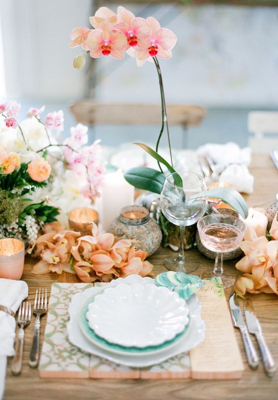 a refined and chic Valentine's Day wedding table with peachy and pink blooms, a wooden placemat, candles and exquisite glasses