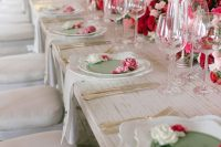 a refined and romantic Valentine's Day wedding table with bold pink and red blooms, candles, refined plates and chic cutlery
