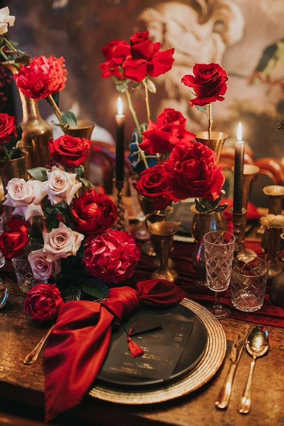 a refined modern Valentine's Day table with blush and red roses, gold candleholders, chargers and cutlery and chic crystal glasses