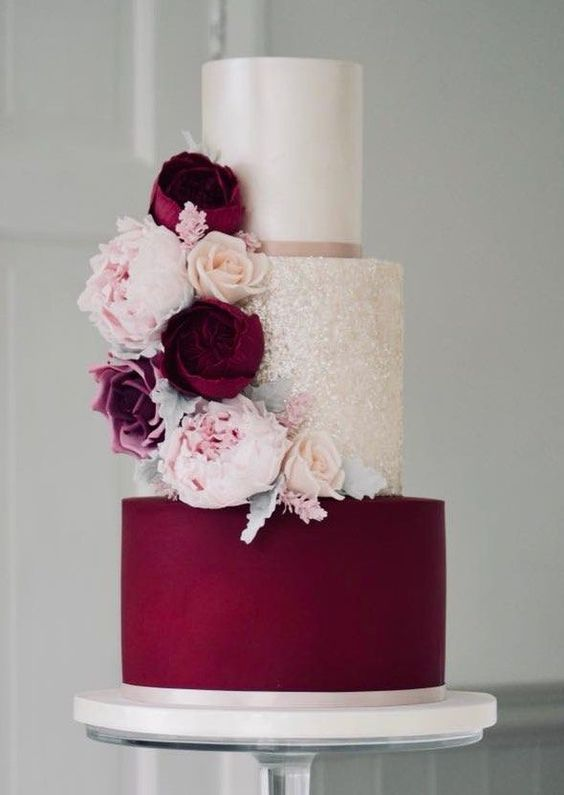 a refined white, gold glitter, purple wedding cake with matching blooms in purple and blush is very chic and stylish