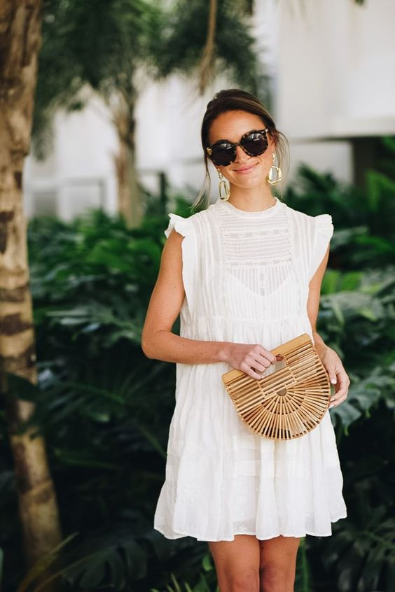a retro-inspired lace mini dress with a high neckline, cap ruffle sleeves and statement earrings and a wooden bag
