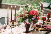 a romantic Valentine's Day wedding table with burgundy napkins, candles and golblets, a pink runner and a bold floral arrangement