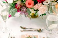 a romantic and chic Valentine's Day wedding tablescape with silver cutlery, bold blooms in blush and fuchsia, glasses and white porcelain