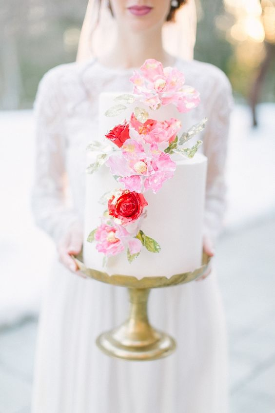 a romantic white wedding cake decorated with pink and red blooms and greenery is a gorgeous idea