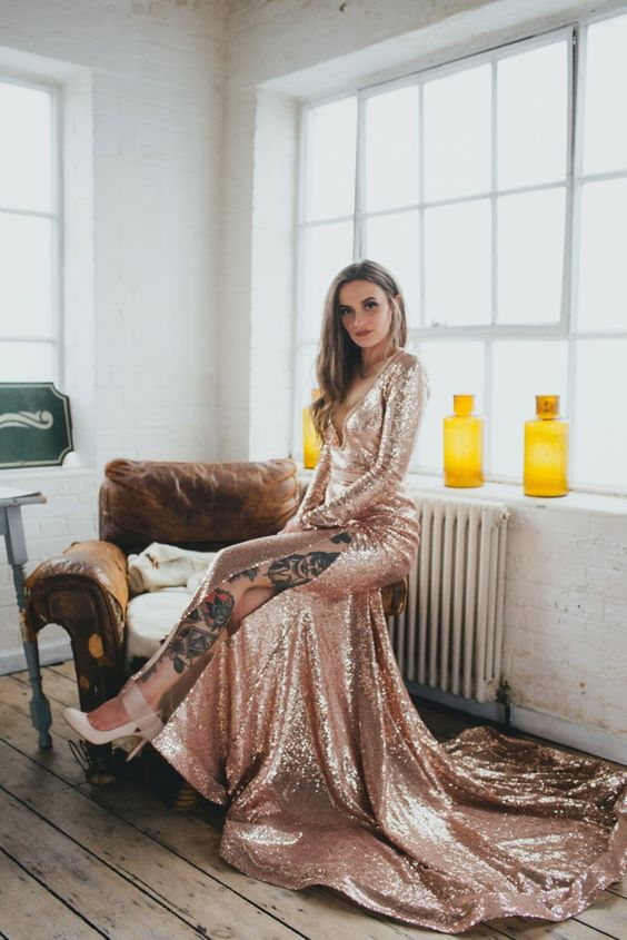 a rose gold sequin A-line wedding dress with long sleeves, a deep neckline, a side slit and a train will make a statement