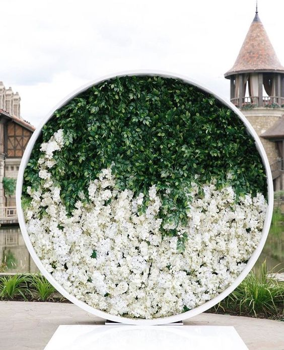 a round flower wall with greenery in the upper part and white blooms in the lower part is a fresh modern idea