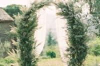 a rustic greenery arbor and wedding chair decor perfectly fit the casual elegance of the Tuscan countryside
