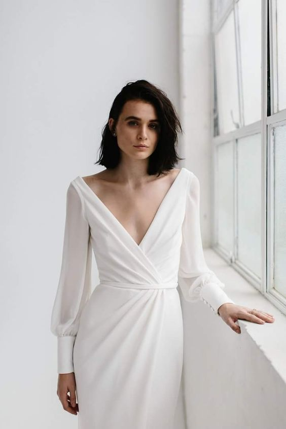 a simple minimalist wedding dress with a deep V-neckline, sleeves on buttons and a bit of drapery