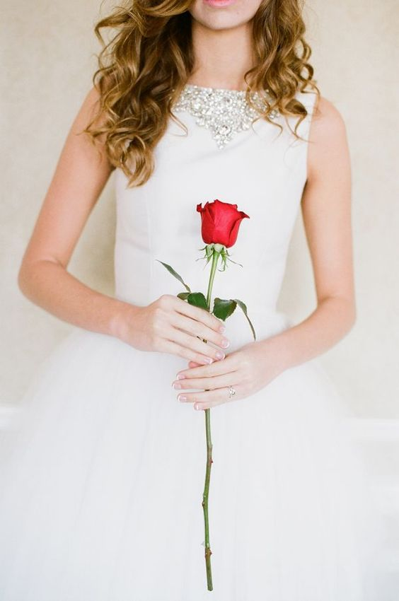 a single red rose used instead of a usual wedding bouquet is a lovely and chic idea for a Valentine bride