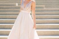 a sleeveless light pink wedding gown with a sequin bodice and a plain full skirt, a plunging neckline