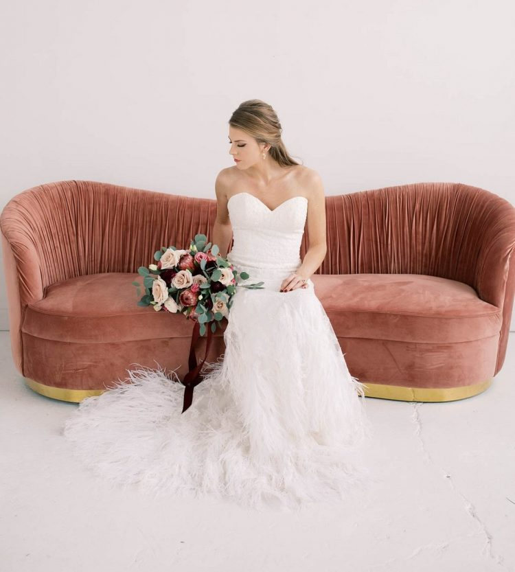 a strapless lace mermaid wedding dress with a feathered skirt and a train is a fabulous and amazing option for a Valentine's Day
