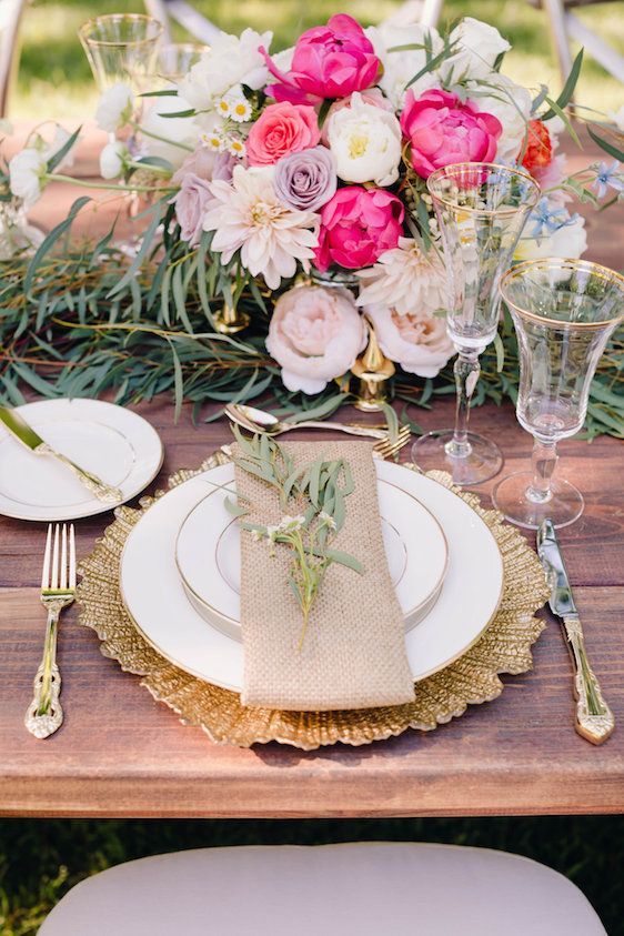 a stunning Valentine's Day wedding table with a greenery runner, a bold pink, lavender and blush floral arrangement, gold cutlery and a charger