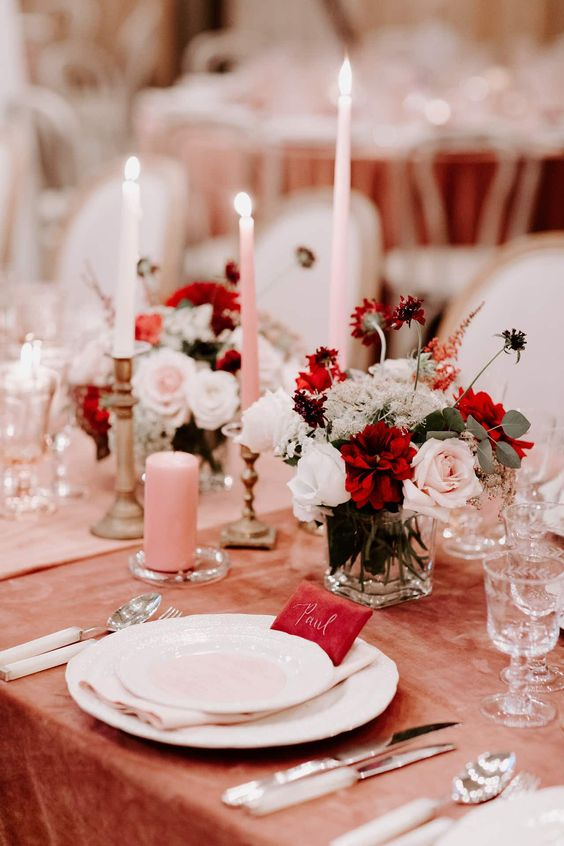 a stunning and catchy Valentine's Day wedding table with a peachy tablecloth and a pink runner, pink candles, blush and burgundy blooms