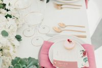 a stylish modern Valentine's Day wedding table with a blush and white floral runner, succulents, pink napkins and gold cutlery