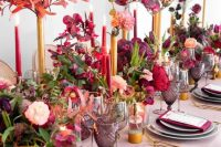 a super colorful Valentine's Day wedding table with a pink tablecloth, grey plates, berry-hued napkins, bold blooms and candles