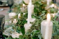 a super lush eucalyptus table runner, concrete candle holders and tall candles for more elegance